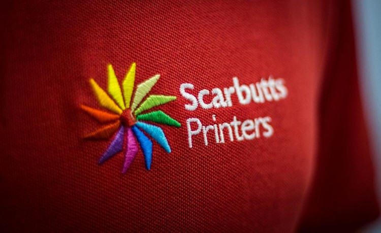 Image of the Scarbutts logo embroidered onto a red polo shirt